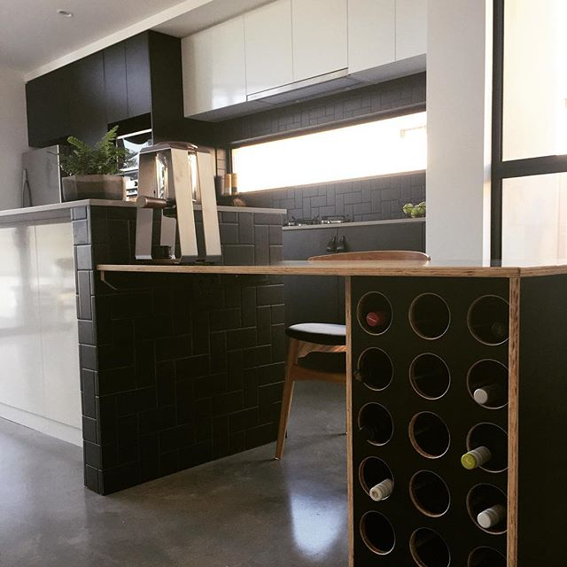 A streamline kitchen with an island counter connected to a dining table