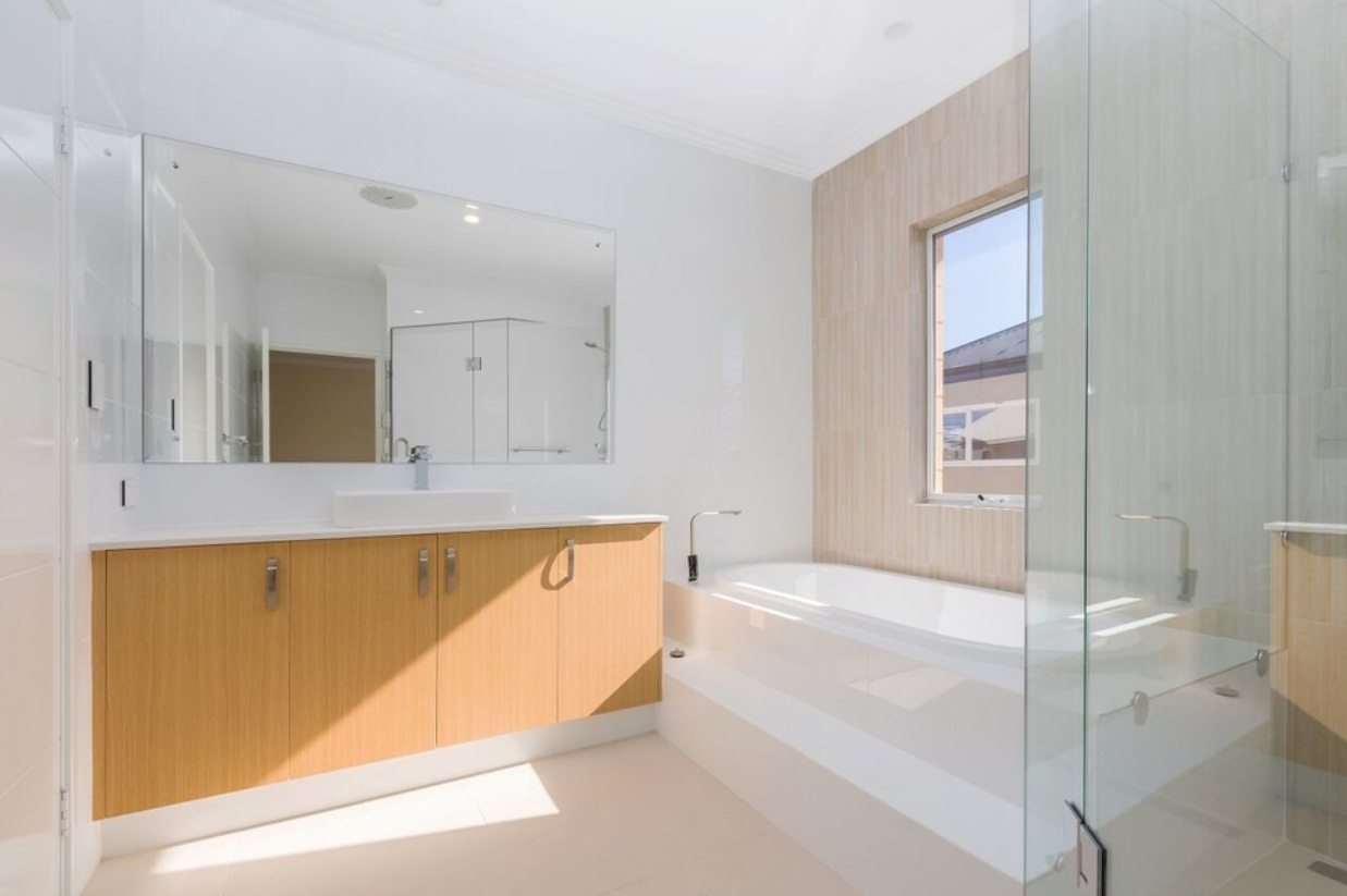 Nice and clean all-white bathroom with a large bathtub and bathroom cabinets