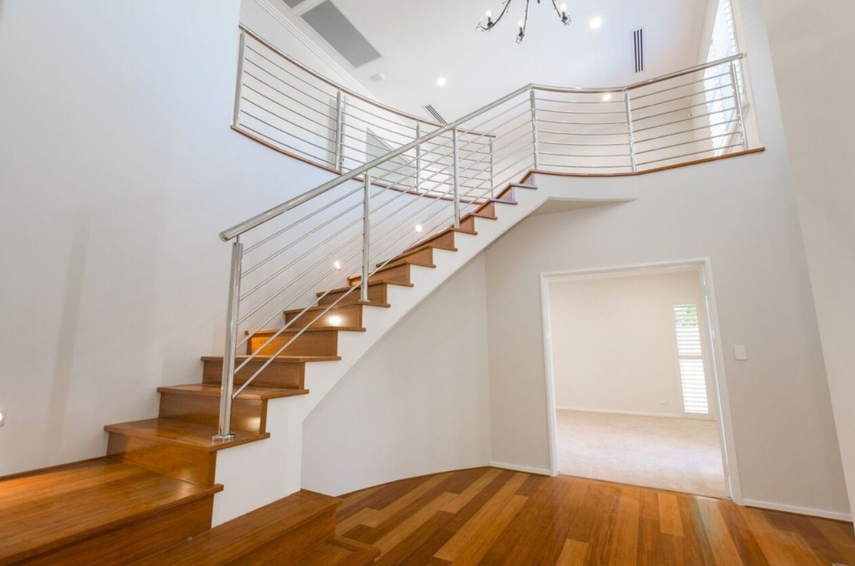 Varnished floor and stairs with a metal railing