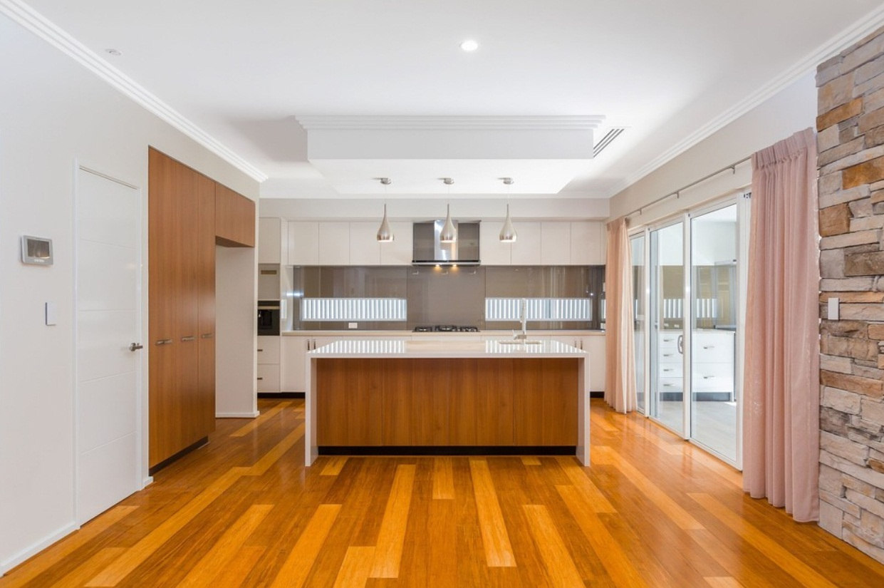 Bright contemporary kitchen with an island in natural wood finish that matches the shade of the natural wood flooring
