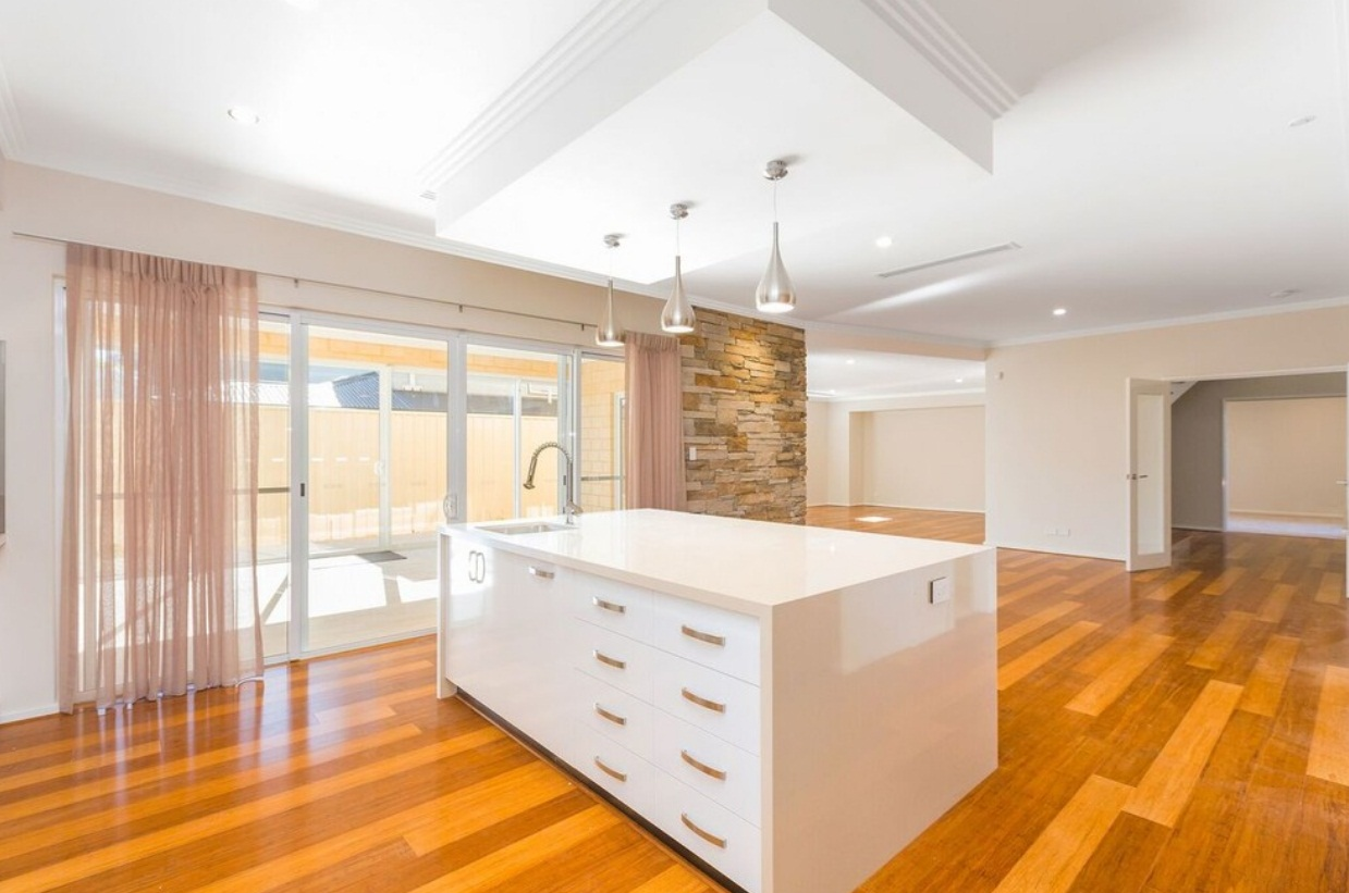 Como style kitchen area with white counter table with sink, white walls and a sliding door