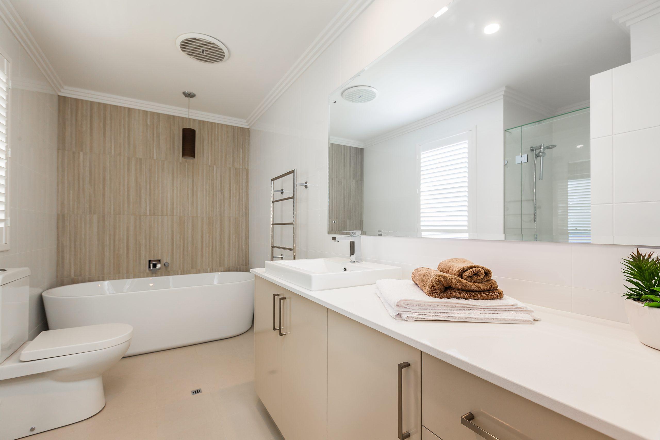 Bathrrom with a large mirror, bathtub, sink and a toilet