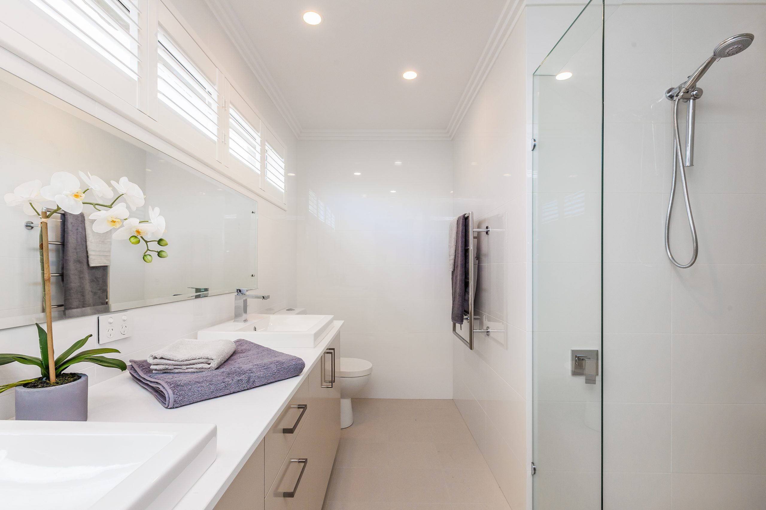 Bathroom with a shower, lavender towels, toilet, mirror and cabinets