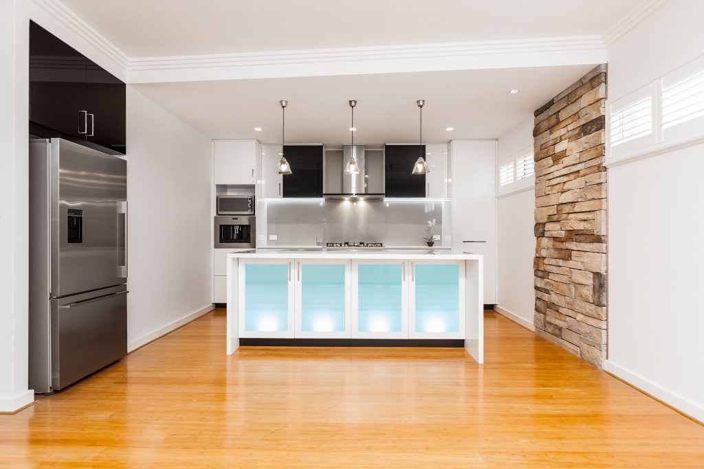 Open kitchen and island counter in white with a stone accent wall and timber flooring