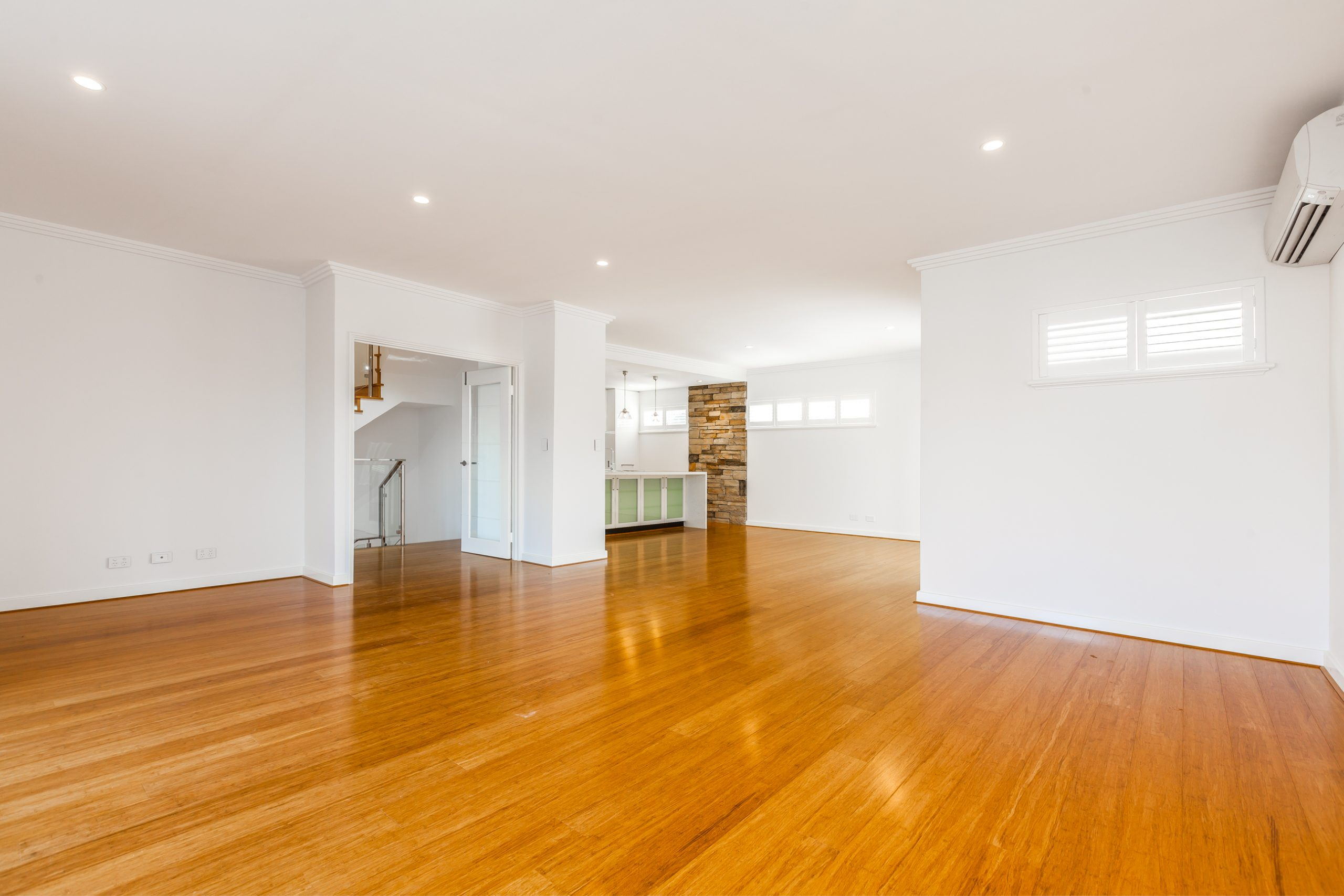 Empty living room with a varnished timber flooring and white walls
