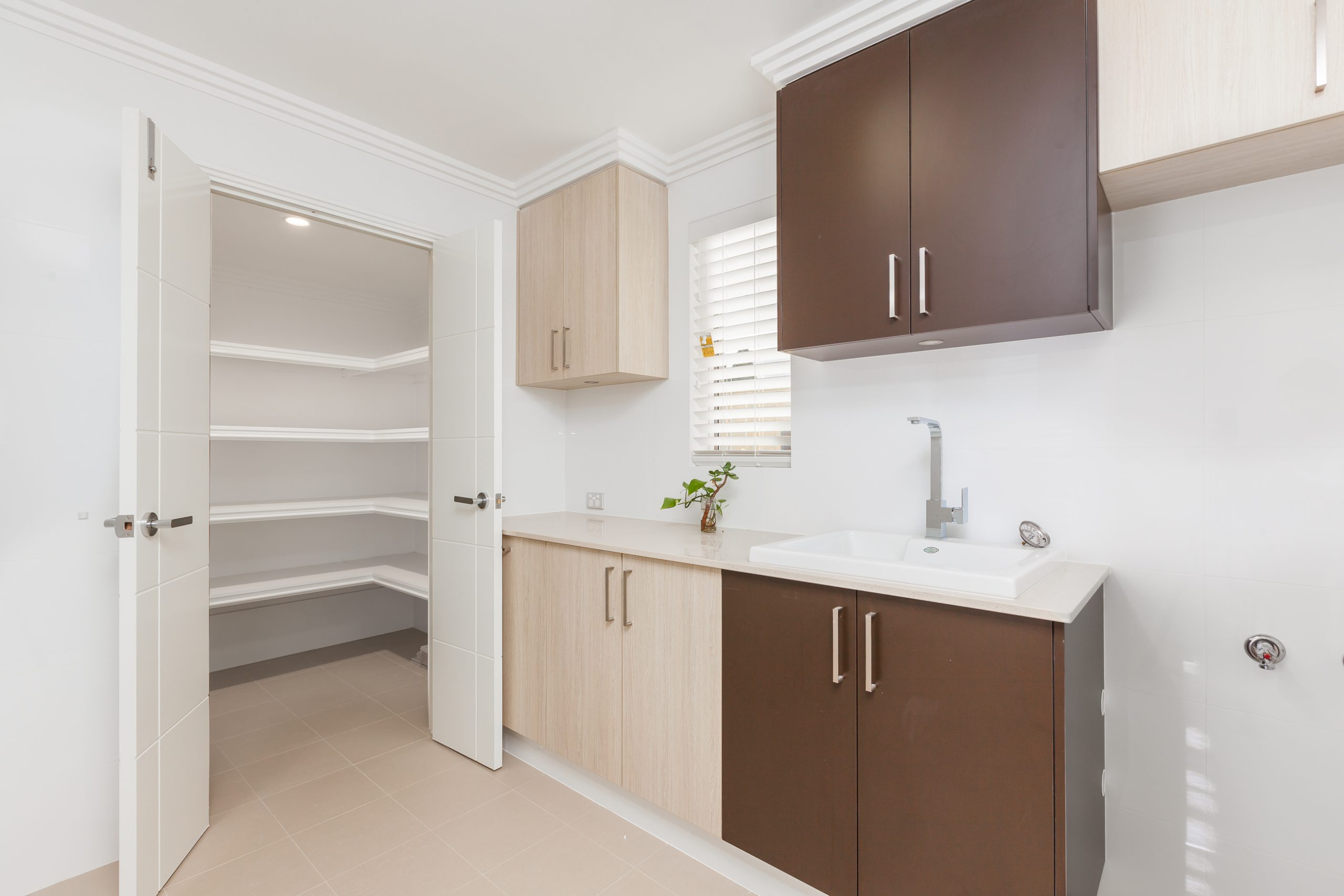 Laundry area with a counter and sink with built in overhead storage, counter cabinets and a linen closet