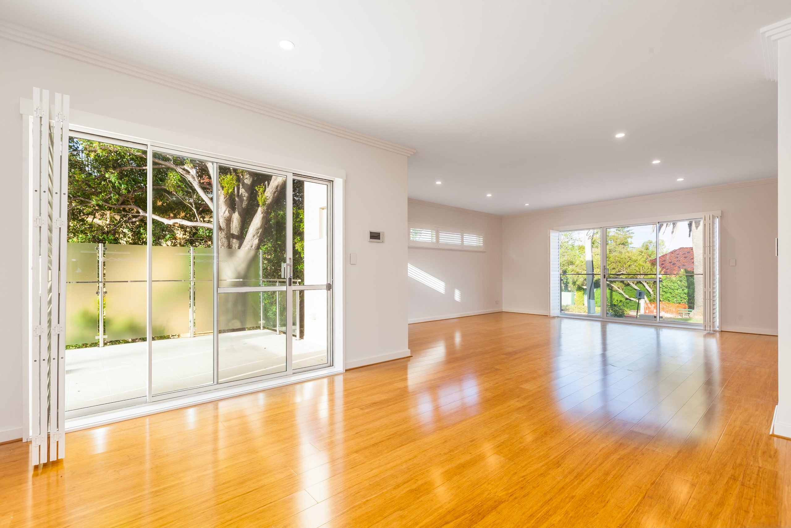 Nedland empty living area with glossy timber flooring, white-painted walls and sliding doors