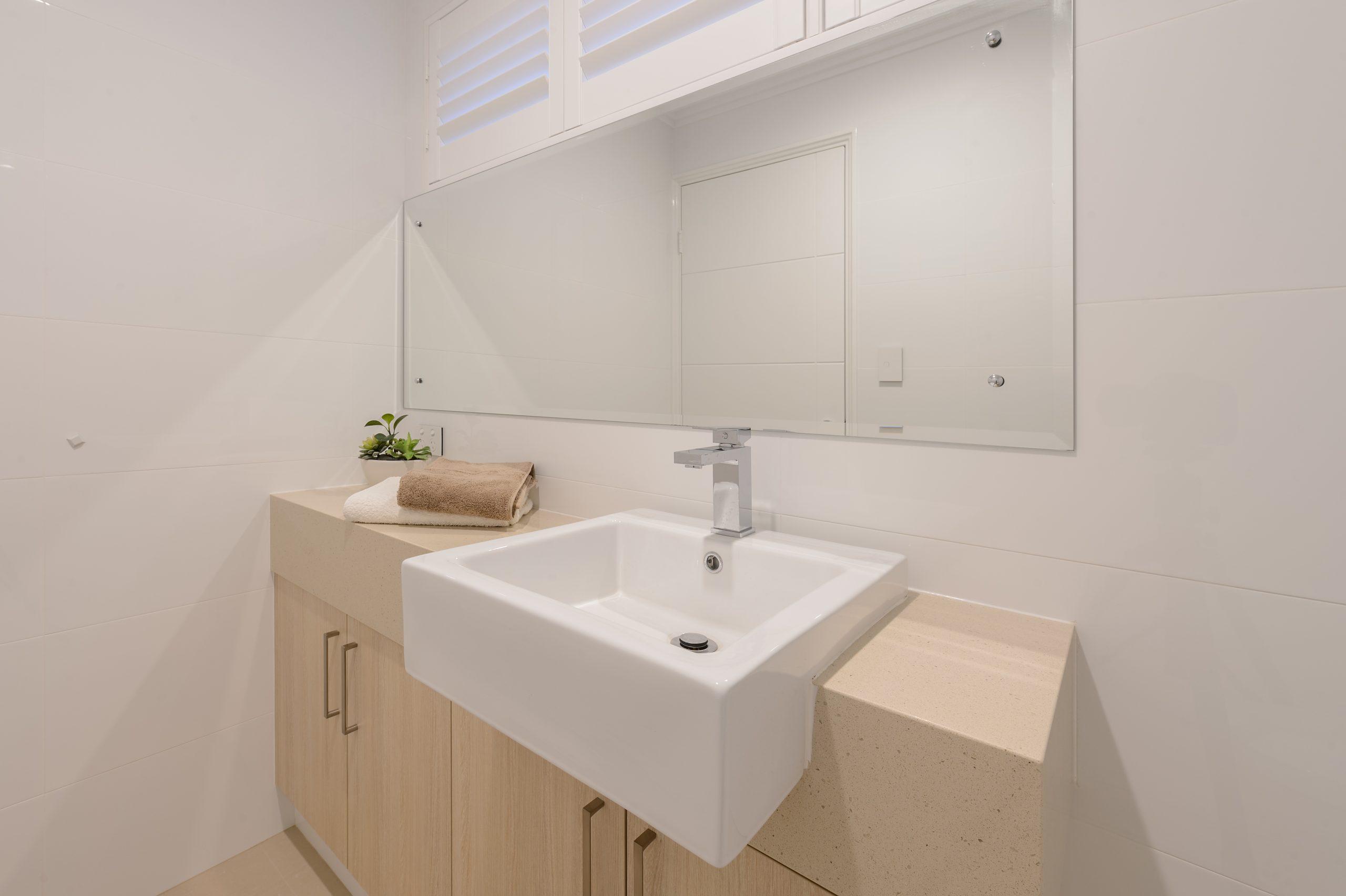 Bathroom with a large bathroom mirror, sink, bathroom cabinets and towels