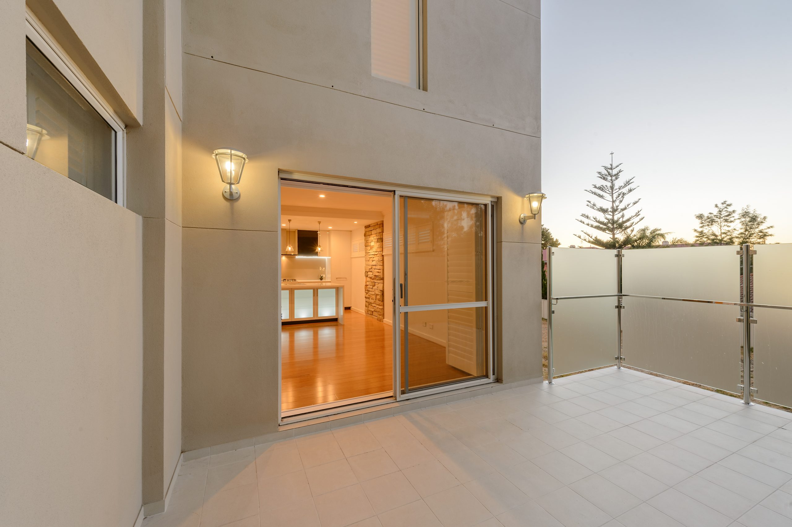 A view of a balcony with frosted glass railing system and and a kitchen