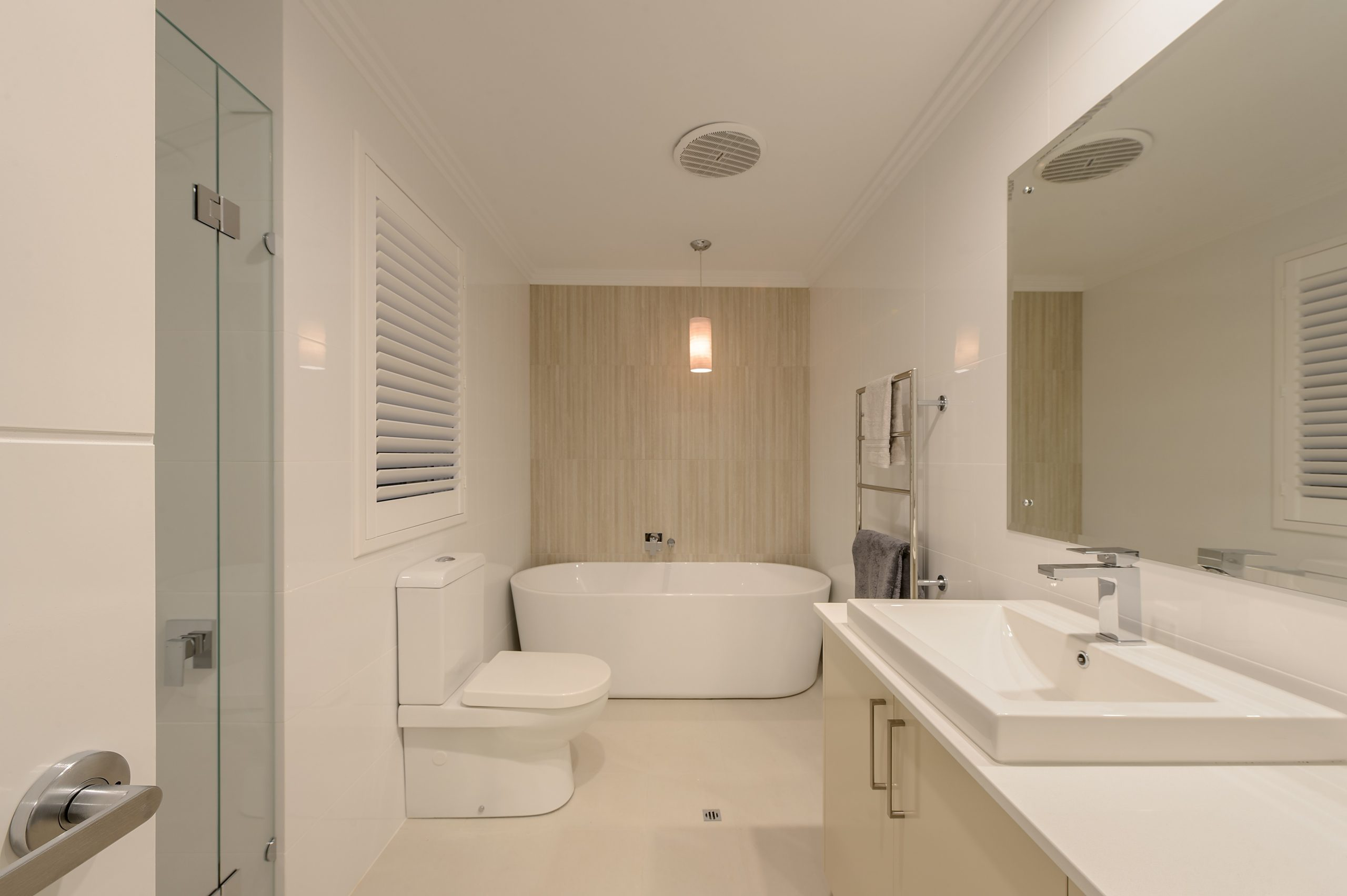 An all white bathroom with a bath tub, sink, toilet, large mirror and a very large louvre
